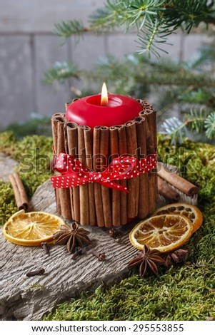 Candle decorated with cinnamon sticks and dried fruits around, christmas decor - stock photo