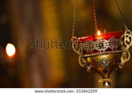Candle flame, covered with gold religious in atmosphere of the church - stock photo