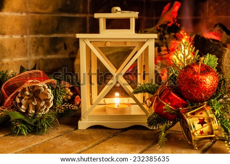 Candle in a candlestick on a background of the fireplace, Christmas decorations on Christmas Eve - stock photo