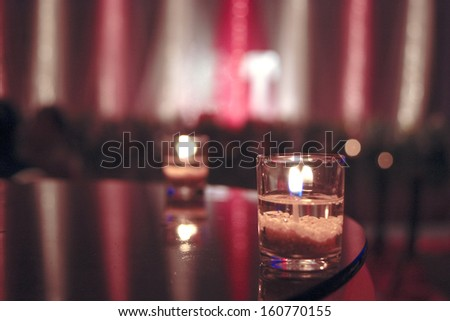 Candle in Glass.background out of focus and donut ring. - stock photo