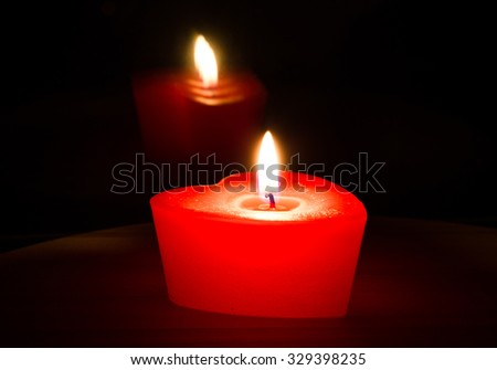 Candle in the form of heart on the table with reflection