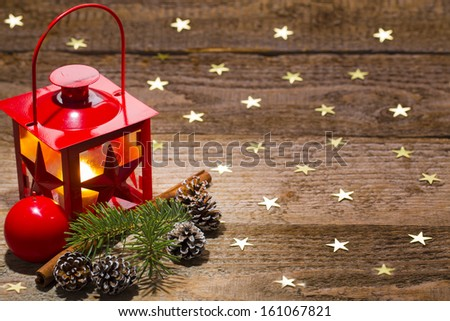 candle lamp, ornament, pine branch, cinnamon and cones on starry old wooden