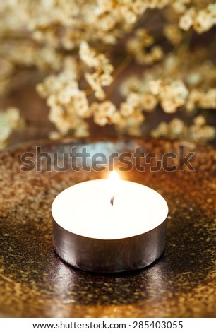 Candle light and flower with focus on a flame - stock photo
