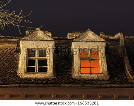 Candle light inside the room, seen on a window under a starry night - stock photo