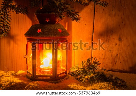 Candle Lit Christmas Lantern under a Fir Branch Covered in Snow