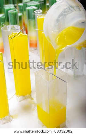 Candle manufacture , pouring colorful molten yellow wax into plastic moulds - stock photo