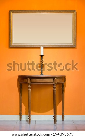 candle on candle stick and old wood table and picture frame on orange wall
