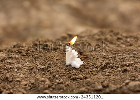 Candle on earth funeral - stock photo