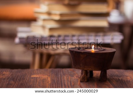 Candle on wooden table with books in background - stock photo