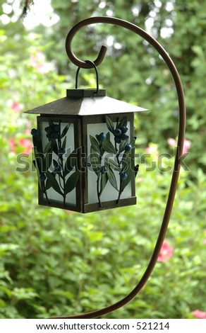 candle-powered lantern decorated with blueberries hanging on a shepherd's hook