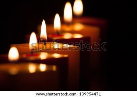 Candle row bokeh in the dark - stock photo