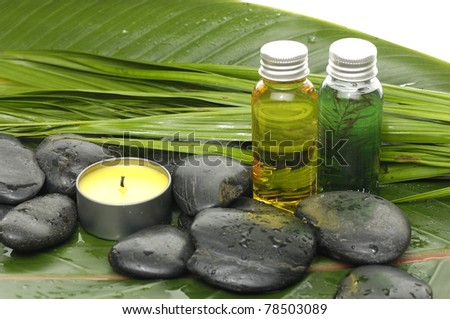 candle with stones on banana leaf background - stock photo