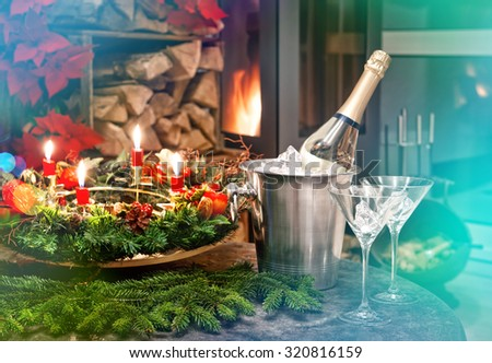 Candlelight dinner. Festive decoration for christmas and new year with bottle of champagne and fireplace. Retro style toned picture with light leaks - stock photo