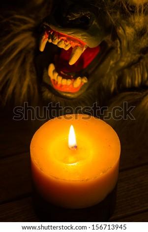 Candlelight illuminating the werewolf face close up - stock photo