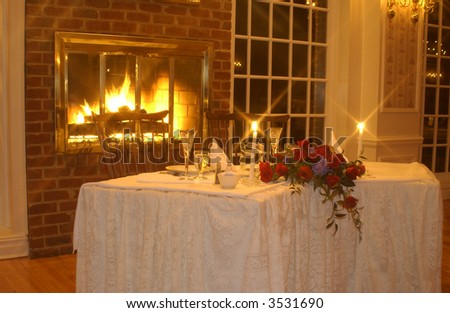 Candlelit Table for Two by fireplace - stock photo