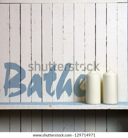 "Candles against rustic bathroom wall; wall is stencilled with the word ""Bathe"" - stock photo"