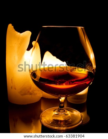candles and a glass of brandy - stock photo