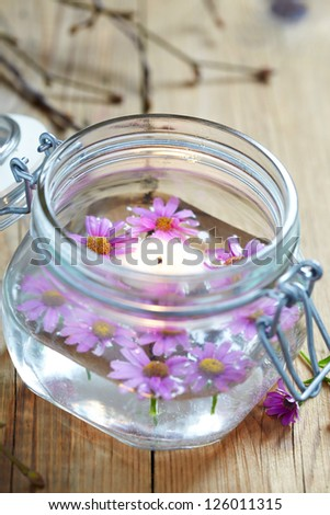 Candles and flowers in glass jar - stock photo