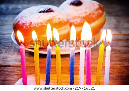 candles and fresh doughnuts with jam on a dark wood background for Hanukkah. tinting. selective focus on the yellow candle - stock photo