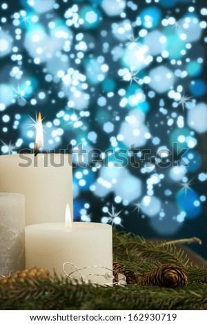 Candles  and Twigs against Blue Bokeh Background - stock photo