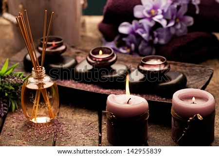 Candles, aromatherapy oil and hot stones used for spa treatments. - stock photo