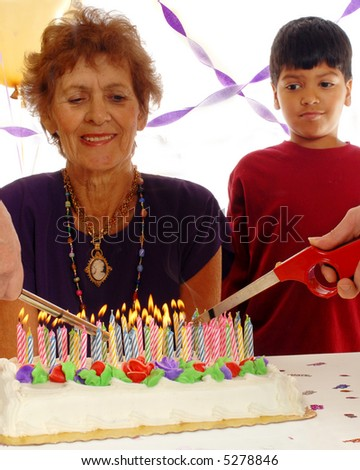 """Candles being lit for an 80 year old's birthday, while the """"birthday girl"""" and a great grandchild looks on.  Isolated on white. - stock photo"""