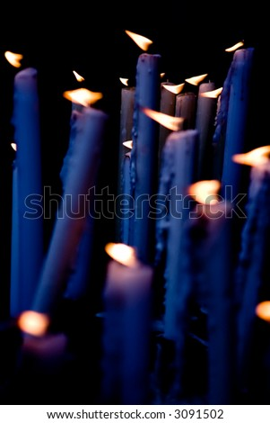 Candles blue tint applied, burning in the altar of the church. - stock photo