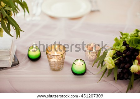 candles, books and flowers on wedding table - stock photo