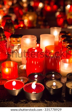 Candles burning at a cemetery during All Saints Day. Shallow depth of field. - stock photo