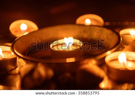 Candles burning at altar in darkness closeup