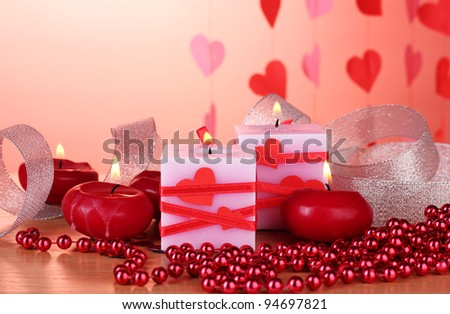 candles for Valentine's Day on wooden table on red background - stock photo