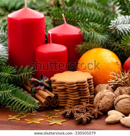 Candles, fruits, cookies and nuts among the spruce twigs - stock photo