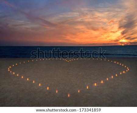 candles heart at sandy sea beach against bright sunset - romantic card concept - stock photo