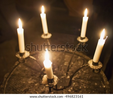 Candles in a candelabrum, in darkness, horizontal image