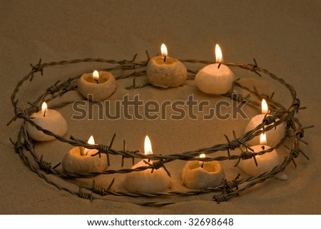 Candles in a ring of barbed wire, symbol of human rights and hope - stock photo