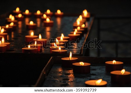 Candles in church. Selective focus on the candles at intersection.  - stock photo