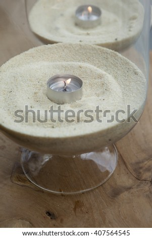 candles in jar  filed with sand - stock photo
