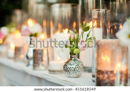 candles in silver glass and small bouquets - stock photo