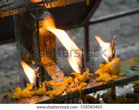 Candles in the wind - candles in Buddhist temple in a windy day
