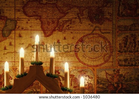 Candles on a background of a puzzled world - stock photo