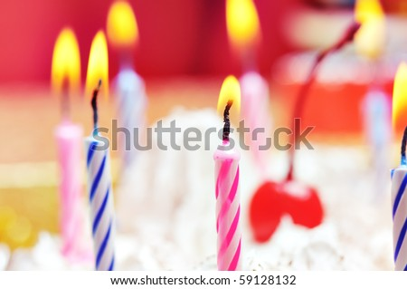 Candles on the birthday cake. Narrow depth of field. Close-up. Orange tint. - stock photo