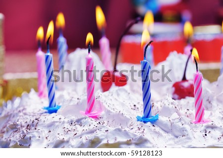 Candles on the birthday cake. Narrow depth of field. Close-up. Violet tint.