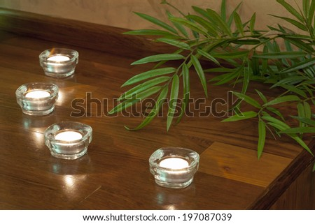 Candles on wooden table in spa center - stock photo