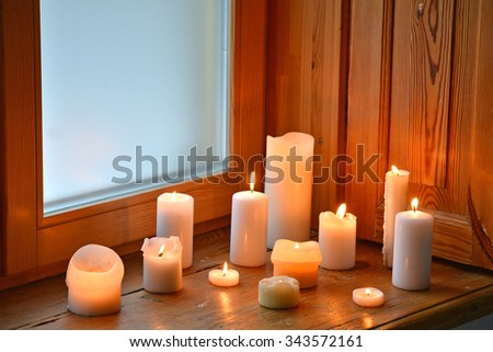 Candles on wooden window sill - stock photo