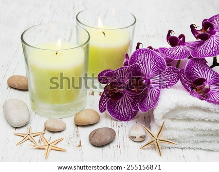 Candles, orcids and towels on a wooden background - stock photo