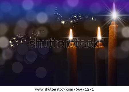 Candles with bright glowing flames on a dark background - stock photo