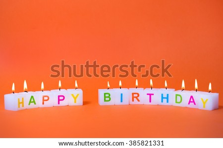 candles with inscription happy birthday on an orange background - stock photo