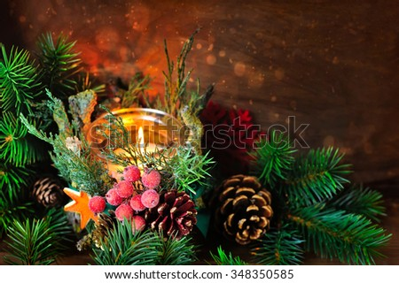 Candlestick and Christmas tree branches on a wooden background. Natural Christmas Decor