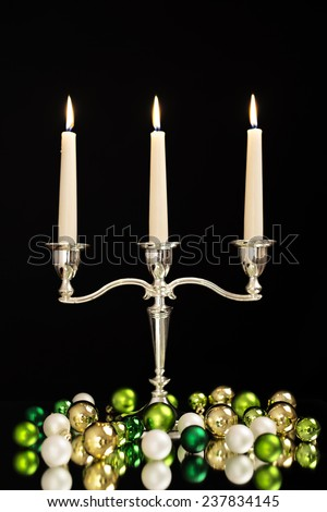 candlestick with three candles, green, gold and pearl Christmas tree balls as Christmas and New Year decoration/Christmas decoration - stock photo
