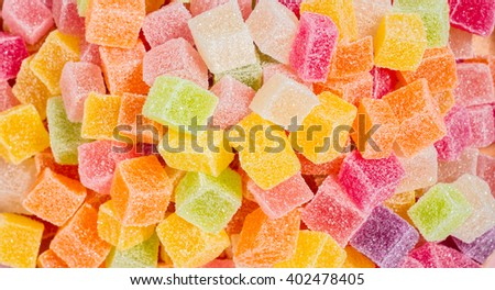 Candy and jelly in dish on pink background